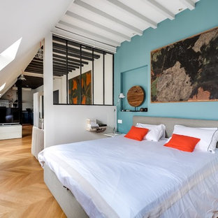 Aménagement d'une chambre contemporaine de taille moyenne avec un mur bleu et un sol en bois brun.
