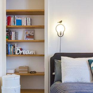Idées déco pour une chambre parentale contemporaine de taille moyenne avec un mur blanc et un sol en bois clair.