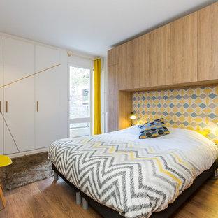 Cette photo montre une petit chambre parentale tendance avec un sol en bois brun, aucune cheminée et un mur marron.