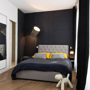Modelo de dormitorio principal, contemporáneo, de tamaño medio, con paredes blancas y suelo de madera en tonos medios