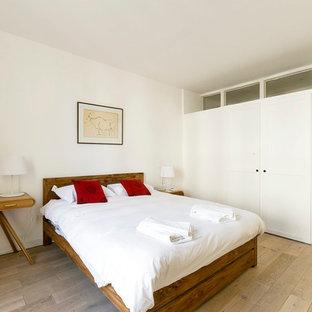 Inspiration pour une grande chambre parentale nordique avec un mur blanc et un sol en bois clair.