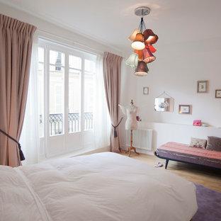 Inspiration pour une chambre parentale bohème de taille moyenne avec un mur blanc, un sol en bois brun, aucune cheminée et un sol marron.
