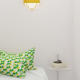 Idée de décoration pour une chambre parentale design de taille moyenne avec un mur blanc.