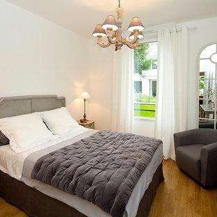 Cette image montre une chambre adulte traditionnelle de taille moyenne avec un mur blanc et un sol en bois brun.