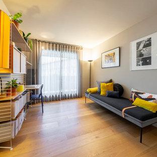 Foto de habitación de invitados moderna, de tamaño medio, sin chimenea, con paredes beige, suelo de madera clara y suelo marrón