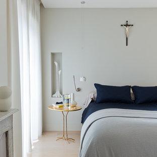 Idées déco pour une chambre contemporaine avec un mur gris, un sol en bois clair et une cheminée standard.