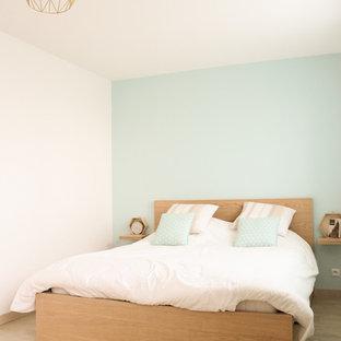 Idée de décoration pour une chambre parentale nordique de taille moyenne avec un sol en bois clair et un mur bleu.
