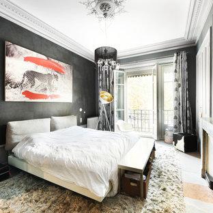 Cette image montre une chambre bohème avec un mur noir, une cheminée standard et un sol gris.