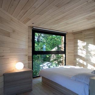 Cette photo montre une chambre tendance avec un mur beige, un sol en bois clair et un sol beige.