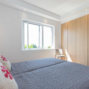 Пример оригинального дизайна: гостевая спальня среднего размера в современном стиле с бежевыми стенами, полом из фанеры и бежевым полом
