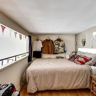 Cette photo montre une chambre tendance avec un mur vert et un sol en bois brun.
