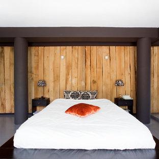 Aménagement d'une grande chambre parentale contemporaine avec un mur marron et béton au sol.