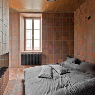 Diseño de dormitorio urbano, pequeño, con paredes marrones, suelo de baldosas de terracota y suelo marrón