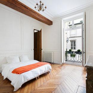 Inspiration pour une très grande chambre parentale traditionnelle avec un mur blanc et un sol en bois brun.