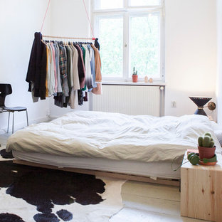 Photo of a medium sized scandinavian master bedroom in Berlin with white walls, painted wood flooring and no fireplace.