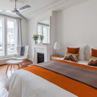 Cette image montre une grand chambre parentale traditionnelle avec un mur blanc, un sol en bois clair et une cheminée standard.