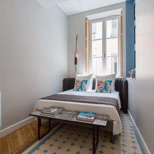 Idée de décoration pour une chambre d'amis bohème avec un mur beige, un sol en bois brun et un sol multicolore.