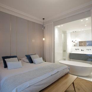 Inspiration pour une grande chambre parentale design avec un mur gris, un sol en bois clair et aucune cheminée.