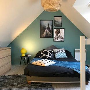 Réalisation d'une chambre design avec un mur vert, un sol en bois clair et un sol gris.