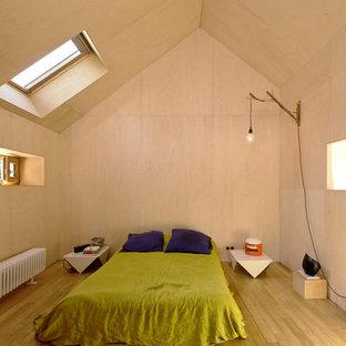 Cette photo montre une chambre tendance avec un mur beige, un sol en bois brun et un sol marron.
