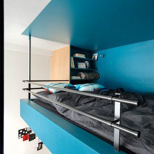 Idées déco pour une chambre mansardée ou avec mezzanine contemporaine avec un mur bleu.