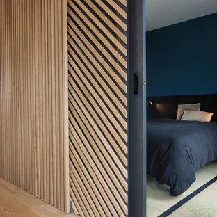На фото: хозяйская спальня среднего размера в современном стиле с синими стенами, татами и белым полом без камина с