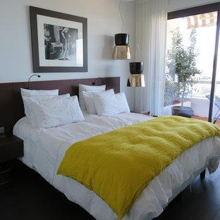 Cette image montre une petite chambre parentale traditionnelle avec un mur blanc et un sol en bois foncé.