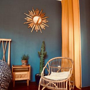 Cette photo montre une chambre parentale rétro avec un mur bleu, un sol en bois foncé et un sol marron.