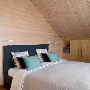 Inspiration pour une chambre d'amis chalet avec un sol en bois brun, un mur marron et aucune cheminée.