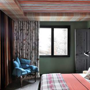 Idée de décoration pour une chambre d'amis bohème avec un mur vert, un sol en bois brun et un sol gris.