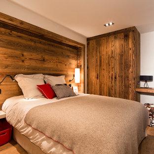 Immagine di una camera matrimoniale stile rurale di medie dimensioni con pareti bianche, pavimento in legno massello medio e nessun camino