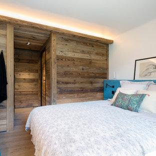 Idées déco pour une chambre parentale montagne de taille moyenne avec un mur blanc, un sol en bois brun et aucune cheminée.
