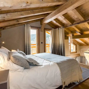 This is an example of a small country loft-style bedroom in Lyon with beige walls, light hardwood floors and no fireplace.