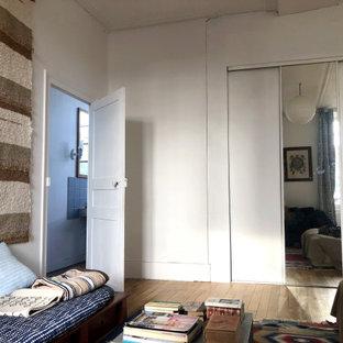 Foto de dormitorio principal, tradicional renovado, extra grande, con paredes blancas, suelo de baldosas de terracota, chimenea tradicional, marco de chimenea de piedra y suelo rosa