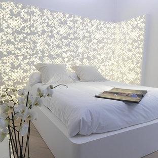 Cette photo montre une chambre parentale tendance avec un mur blanc et un sol en bois clair.