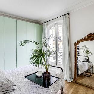 Réalisation d'une chambre parentale tradition avec un mur blanc, un sol en bois clair et aucune cheminée.