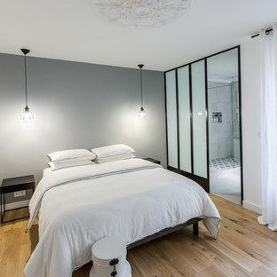 Cette image montre une chambre parentale design de taille moyenne avec un mur gris, un sol en bois clair et aucune cheminée.