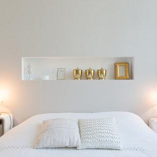Inspiration pour une petit chambre parentale design avec un mur blanc et un sol en bois clair.
