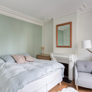 Exemple d'une chambre parentale scandinave de taille moyenne avec un mur vert, un sol en bois brun, une cheminée standard, un manteau de cheminée en plâtre et un sol marron.