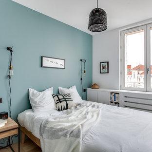 Imagen de dormitorio principal, nórdico, pequeño, con paredes azules y suelo de madera clara