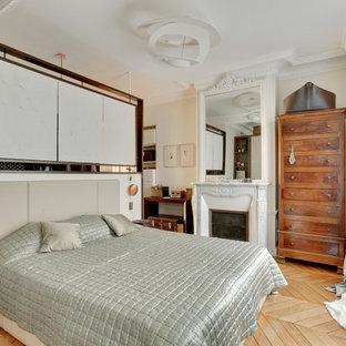 Exemple d'une chambre parentale chic de taille moyenne avec un mur blanc, un sol en bois clair, une cheminée standard et un sol marron.