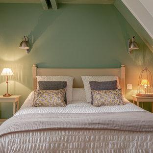 Imagen de habitación de invitados tradicional renovada, de tamaño medio, sin chimenea, con paredes verdes, suelo laminado y suelo marrón