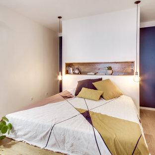 Cette image montre une chambre d'amis design de taille moyenne avec un sol en bois clair, un sol beige et un mur beige.
