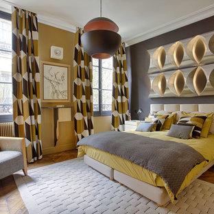 Exemple d'une grande chambre parentale rétro avec un mur jaune, un sol en bois clair, aucune cheminée et un sol marron.