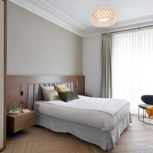 Exemple d'une chambre tendance avec un mur gris, un sol en bois brun et un sol marron.