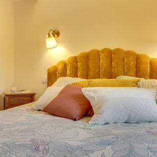 Modelo de dormitorio principal, retro, pequeño, con parades naranjas, suelo laminado y suelo marrón