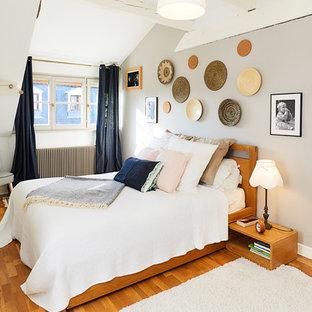 Idée de décoration pour une chambre parentale tradition de taille moyenne avec un sol marron, un mur blanc et un sol en bois clair.