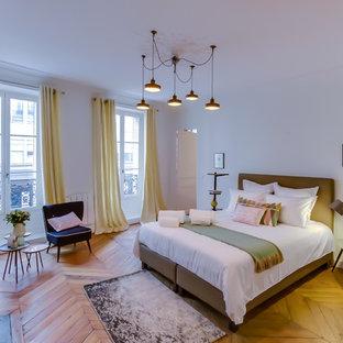 Esempio di una grande camera matrimoniale scandinava con pareti bianche, parquet chiaro, camino classico e cornice del camino in pietra