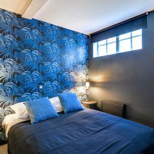 Ejemplo de dormitorio principal, exótico, pequeño, con paredes azules, suelo laminado y suelo gris