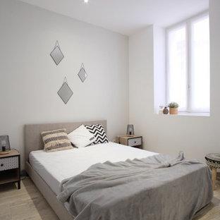 Ejemplo de dormitorio de tamaño medio con paredes beige y suelo de travertino
